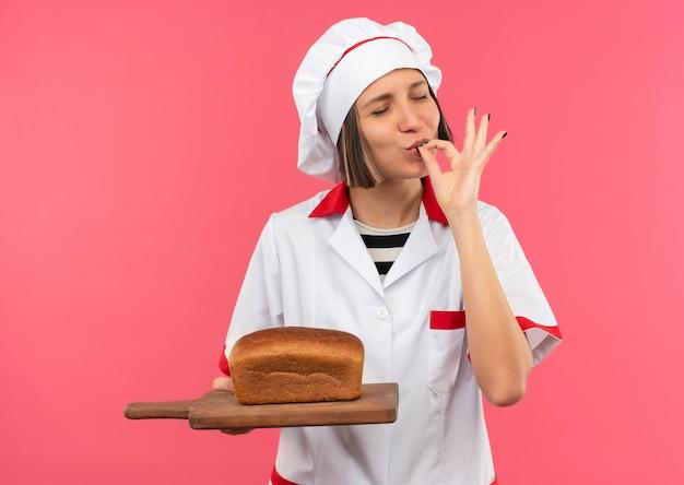 Erfreute junge köchin in der kochuniform, die schneidebrett mit brot darauf hält und leckere geste mit geschlossenen augen tut, die auf rosa hintergrund lokalisiert werden