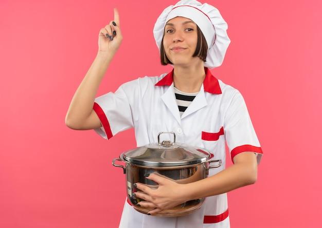 Erfreute junge köchin in der kochuniform, die topf hält und lokal auf rosa wand zeigt