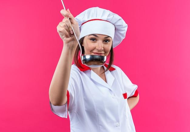 Erfreute junge köchin in kochuniform, die die schöpfkelle vorne isoliert auf rosa wand hält