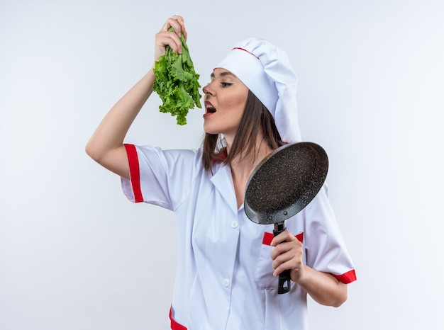 Erfreute junge köchin in kochuniform, die salat mit bratpfanne isoliert auf weißer wand hält
