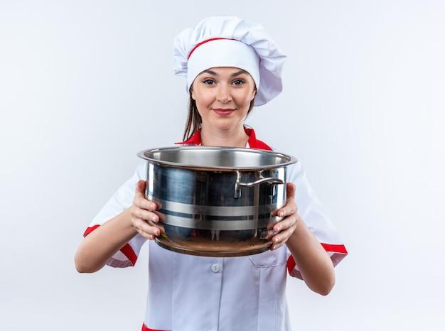 Erfreute junge köchin in kochuniform mit kochtopf isoliert auf weißer wand