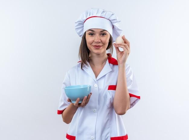 Erfreute junge köchin in kochuniform mit schüssel mit ei isoliert auf weißer wand