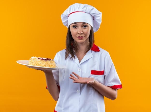 Erfreute junge köchin mit kochuniform, die mit der hand auf den kuchen auf dem teller auf orangefarbenem hintergrund zeigt