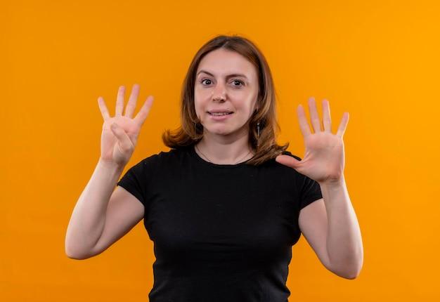 Erfreute junge lässige frau, die vier und fünf auf isoliertem orangefarbenem raum zeigt