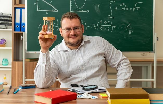 Erfreute junge lehrerin mit brille, die am schreibtisch mit schulmaterial im klassenzimmer sitzt und die hand auf der taille hält und nach vorne schaut und eine sanduhr zeigt