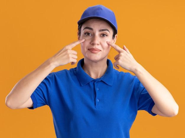 Erfreute junge lieferfrau in uniform und mütze, die mit den fingern auf die wangen zeigt, die auf der orangefarbenen wand isoliert sind?