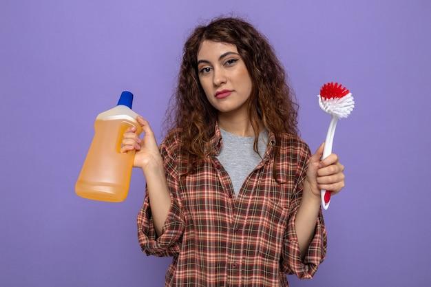Erfreute junge putzfrau, die reinigungsmittel mit reinigungsbürste hält
