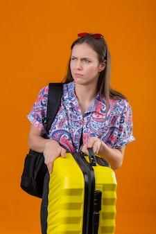 Erfreute junge reisende frau, die rote sonnenbrille auf kopf stehend mit rucksack hält, der koffer mit stirnrunzelndem gesicht beiseite schaut