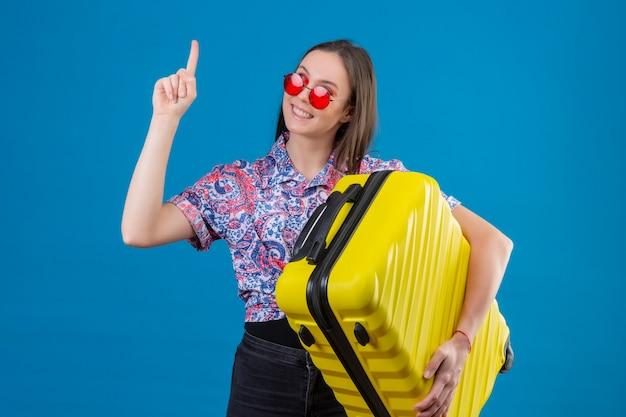 Erfreute junge reisende frau, die rote sonnenbrille hält, die gelben koffer mit finger nach oben hält und zuversichtlich aussieht, große idee über blaue wand zu haben