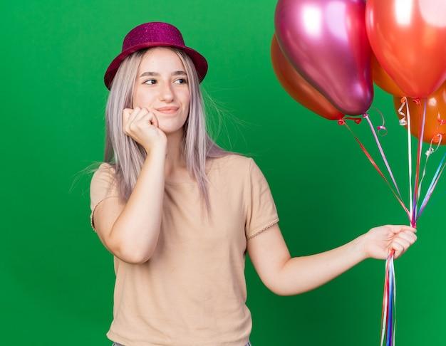 Erfreute junge schöne frau mit partyhut, die luftballons hält, die hand auf die wange legt, isoliert auf grüner wand