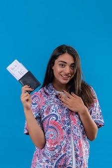 Erfreute junge schöne reisende frau, die mit tickets und pass händchenhalten auf der brust dankbar lächelnd freundlich über blauem hintergrund steht