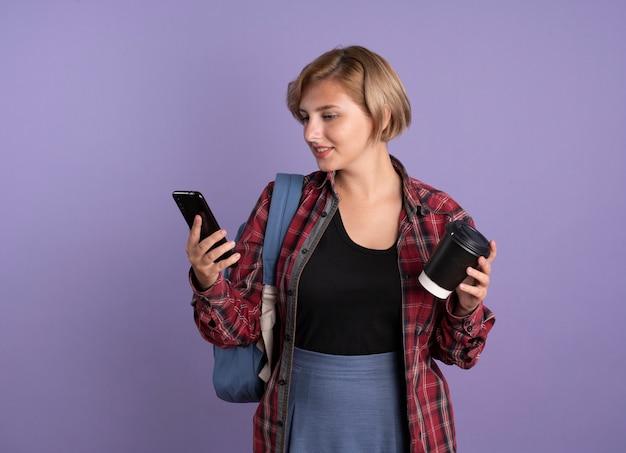 Erfreute junge slawische studentin mit rucksack hält pappbecher und schaut auf telefon