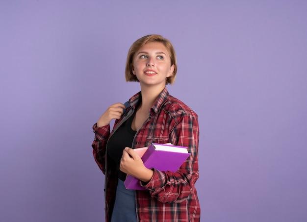 Erfreute junge slawische studentin mit rucksack steht seitlich und hält buch und notizbuch