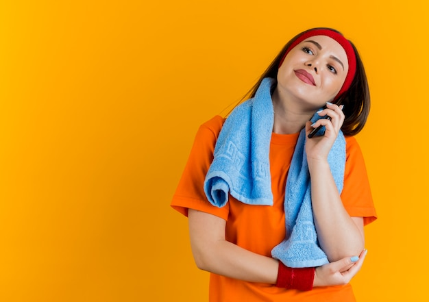 Erfreute junge sportliche frau, die stirnband und armbänder mit handtuch um den hals trägt und seite betrachtet, die hand auf ellbogen setzt und am telefon spricht