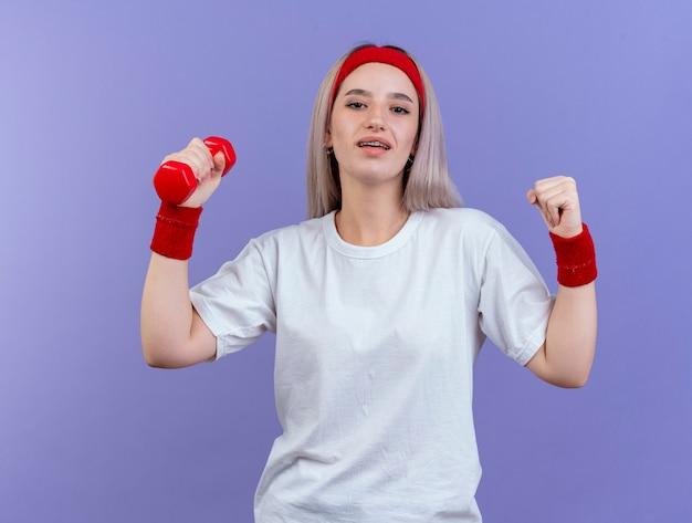 Erfreute junge sportliche frau mit hosenträgern, die stirnband und armbänder tragen, hält faust und hantel isoliert auf lila wand