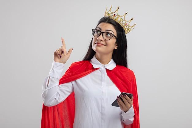 Erfreute junge superfrau, die brille und krone hält handy hält und lokalisiert auf weißer wand zeigt