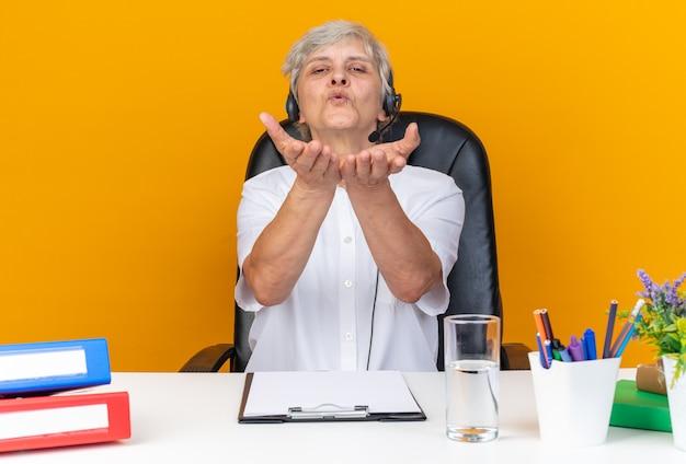 Erfreute kaukasische callcenter-betreiberin auf kopfhörern, die am schreibtisch mit bürowerkzeugen sitzen und einen kuss mit händen auf orangefarbener wand senden