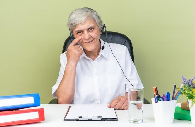 Erfreute kaukasische callcenter-betreiberin auf kopfhörern, die am schreibtisch mit bürowerkzeugen sitzen und ihren finger auf das augenlid legen, isoliert auf grüner wand