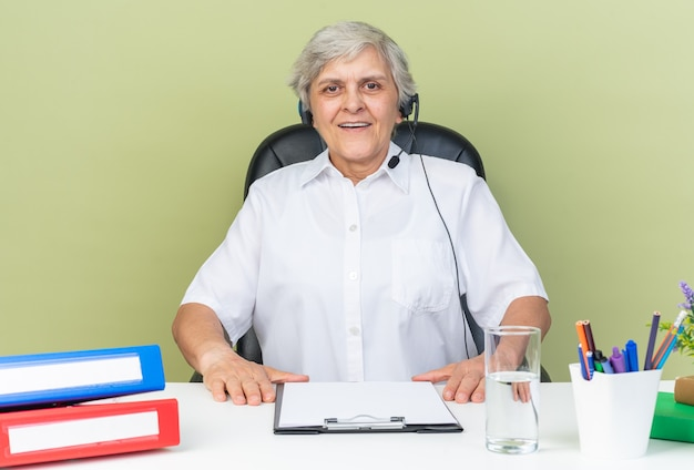 Erfreute kaukasische callcenter-betreiberin mit kopfhörern, die am schreibtisch mit bürowerkzeugen isoliert auf grüner wand sitzen