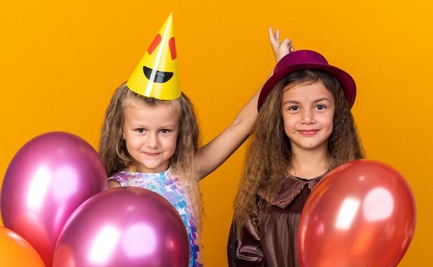 Erfreute kleine hübsche mädchen mit partyhüten, die heliumballons isoliert auf oranger wand mit kopierraum halten