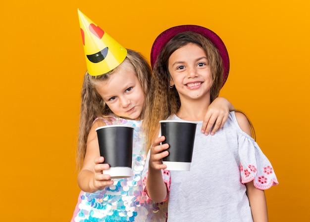 Erfreute kleine hübsche mädchen mit partyhüten, die pappbecher isoliert auf oranger wand mit kopierraum halten