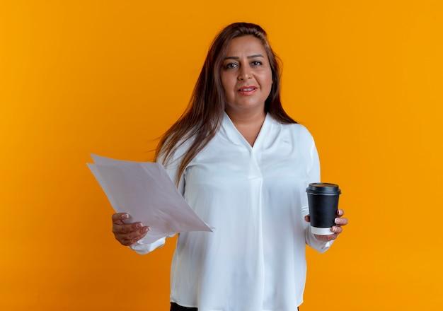 Erfreute lässige kaukasische frau mittleren alters, die papier und tasse kaffee hält