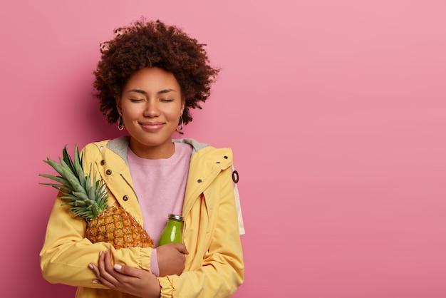 Erfreute lockige afroamerikanische frau hat gesunde ernährung