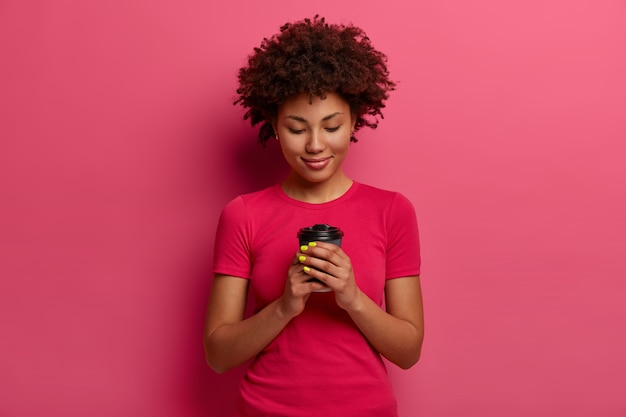 Erfreute lockige frau hält pappbecher kaffee, genießt freizeit, hat pause, trinkt heißes getränk, wärmt sich mit tee auf, gekleidet in lässiges t-shirt, isoliert auf rosa wand. trinkkonzept