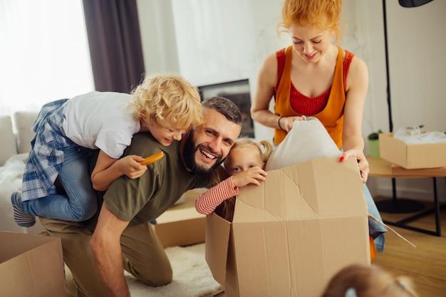 Erfreute nette familie, die anfängt, in einem neuen haus zu leben