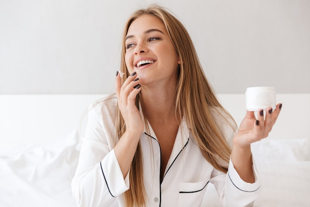 Erfreute nette frau im pyjama, die creme aufträgt und lächelt, während sie im hellen raum auf dem bett sitzt?