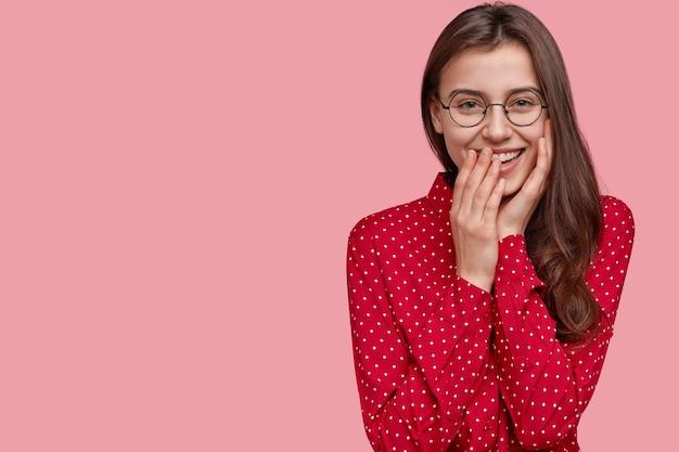 Erfreute optimistische dame öffnet den mund vor faszination und aufregung, bedeckt den mund mit der hand, elegant gekleidet, reagiert positiv auf unerwartete gute nachrichten