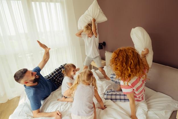 Erfreute positive familie mit einer kissenschlacht
