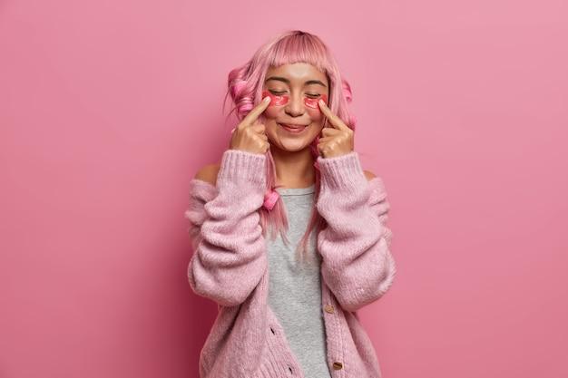 Erfreute positive frau hat langes rosiges haar, macht lockige frisur mit lockenwicklern, zeigt auf schönheitsflecken, steht mit geschlossenen augen und trägt warmen pullover