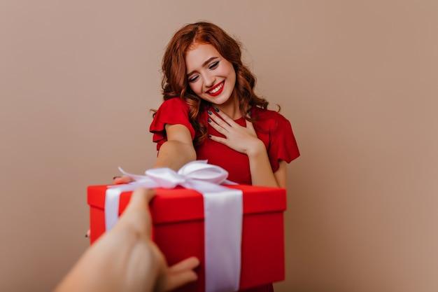 Erfreute rothaarige frau, die weihnachtsgeschenke genießt. interessiertes lächelndes mädchen, das neues jahr feiert.