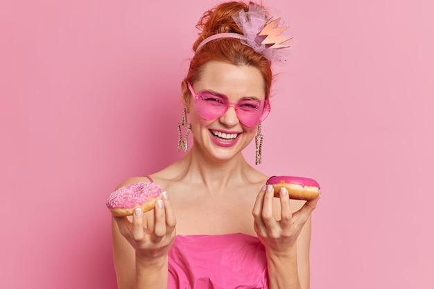 Erfreute rothaarige frau drückt positive gefühle aus, hält zwei appetitliche donuts und lächelt glücklich, gut gelaunt zu sein