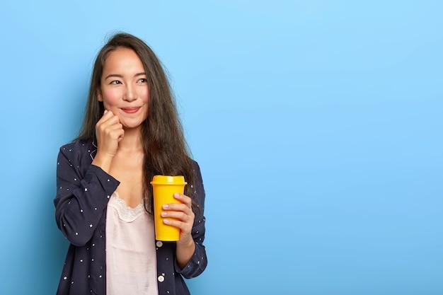 Erfreute schöne brünette asiatische frau hat verträumten gesichtsausdruck, überlegt, was an diesem tag zu tun ist, wacht früh auf, trinkt erfrischten kaffee