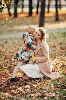 Erfreute schöne dame, die auf ihren knien im park sitzt und lächelt, während ein süßes mädchen sie in den blättern umarmt.