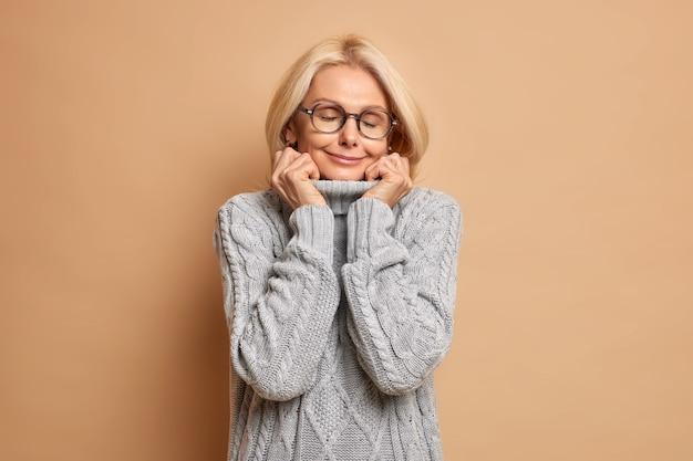 Erfreute schöne frau mittleren alters hält hände am kragen von warmen pulloverständern mit geschlossenen augen trägt brille erinnert an etwas angenehmes.