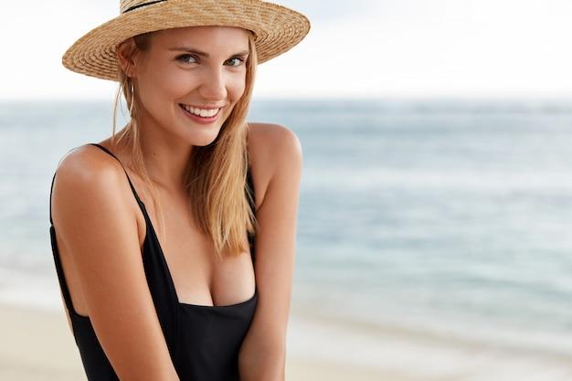 Erfreute schöne junge frau mit attraktiver guter laune, trägt sommermütze und schwarzen badeanzug, posiert gegen schönen meerblick. frau verbringt zeit in ferieninsel
