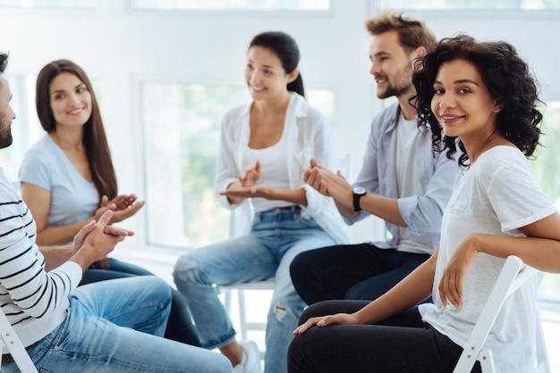 Erfreute schöne positive frau, die sie ansieht und lächelt, während sie mit anderen patienten im kreis sitzen