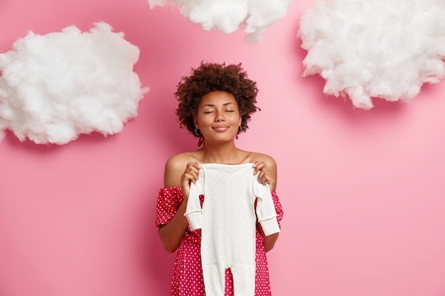 Erfreute schwangere frau hält baby strampler über bauch, bereitet kinderkleidung vor, steht mit geschlossenen augen, macht sich bereit für das entbindungsheim, posiert gegen rosa wand mit wolken. mutterschaftskonzept