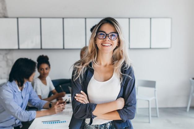 Erfreute sekretärin in trendiger brille posiert im büro nach einem treffen mit kollegen. innenporträt der stilvollen geschäftsfrau mit asiatischen und afrikanischen arbeitern.