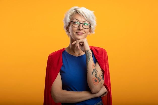 Erfreute superfrau mit rotem umhang in optischer brille legt hand auf kinn und schaut auf seite isoliert auf orange wand