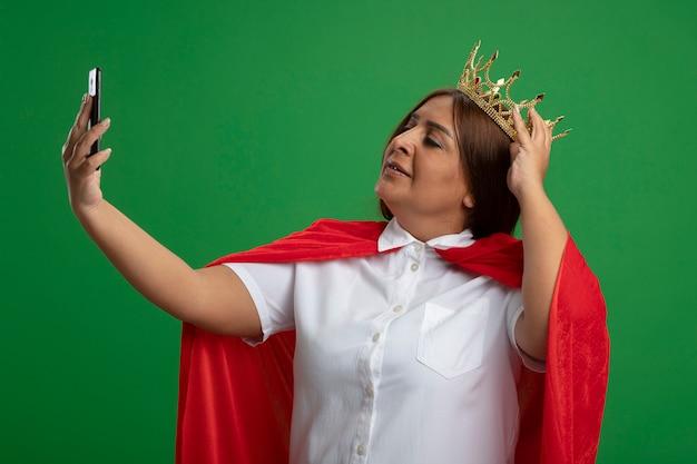 Erfreute superheldenfrau mittleren alters, die krone trägt, nehmen ein selfie, das hand auf krone lokalisiert auf grün setzt