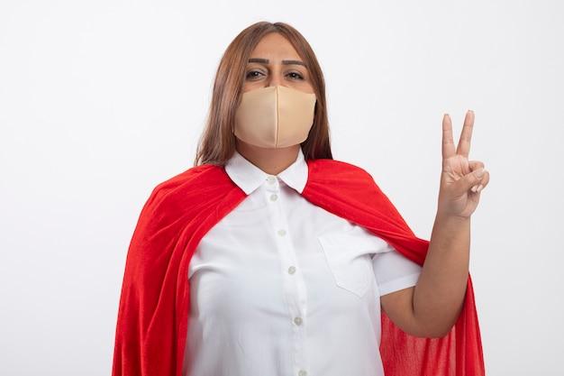 Erfreute superheldenfrau mittleren alters, die medizinische maske trägt, die friedensgestik lokalisiert auf weiß zeigt