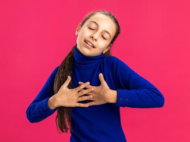 Erfreute teenager-mädchen tun danke geste mit geschlossenen augen isoliert auf rosa wand