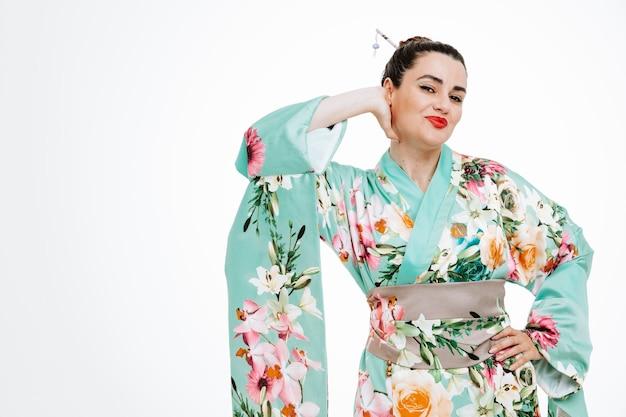 Erfreute und glückliche frau im traditionellen japanischen kimono, die hand auf dem kopf und der anderen hand auf der hüfte auf weiß lächelnd hält