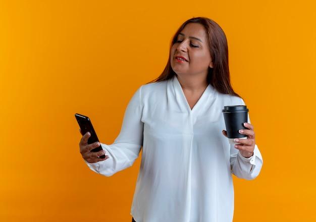 Erfreute zufällige kaukasische frau mittleren alters, die tasse kaffee hält und telefon in ihrer hand betrachtet
