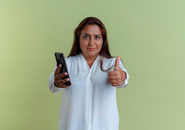 Erfreute zufällige kaukasische frau mittleren alters, die telefon hält und ihren daumen nach oben zeigt