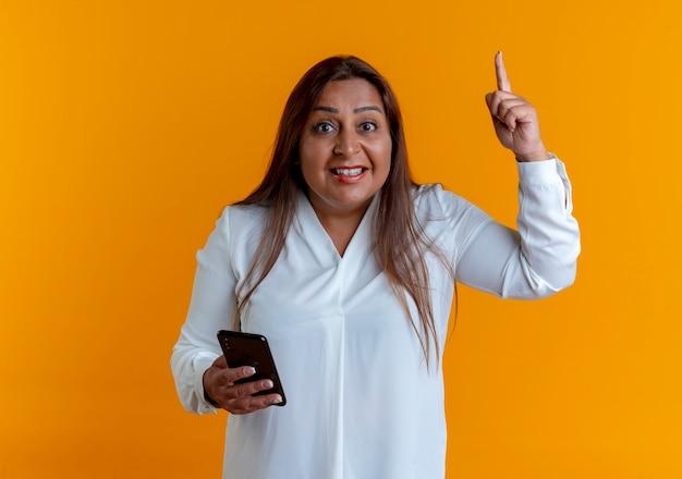 Erfreute zufällige kaukasische frau mittleren alters, die telefon hält und nach oben zeigt